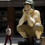 """Segurança admirando uma escultura de Roberto Bolaños do personagem """"CHAVES"""" e """"CHAPOLIN"""""""