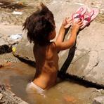Utilidade Pública - Assistentes sociais buscam menina fotografada tomando banho em bueiro no RJ