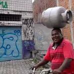 Homem equilibra botijão de gás na cabeça enquanto anda de bicicleta